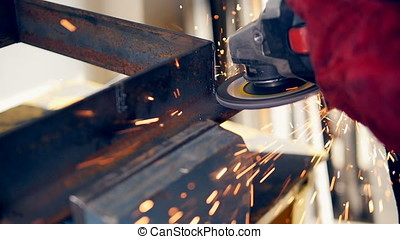 Grinding power tool in use, sparks. Close up. Slow motion. -...