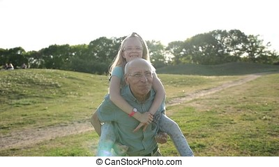 Grandfather giving granddaughter piggyback ride - Handsome...