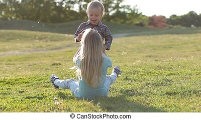 Two cute children playing together in green field - Joyful...