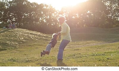 Happy grandmother spinning grandson in circle