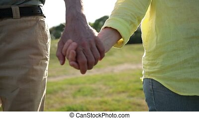 Closeup of seniors holding hands expressing love and support...