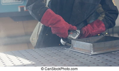 Worker using grinder wearing red protective gloves, sparks....