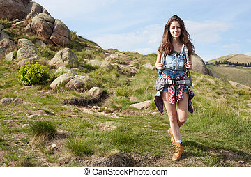 Traveling girl with backpack hiking in the mountains, eco...