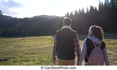 young couple walking along the lake