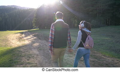 young couple walking along the lake at sunset