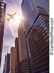 plane over office towers - plane flying over futuristic...
