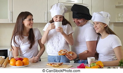 happy family having Breakfast together. father, mother and two daughters gathered together in the kitchen and having fun