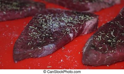 Sprinkling raw steak with salt