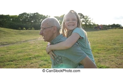Cute smiling girl enjoying piggyback ride in park - Adorable...