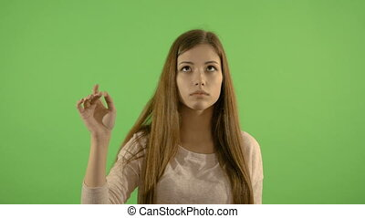 Beautiful girl shows gestures on an imaginary tablet. On the...