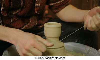 Professional male potter working in workshop, studio