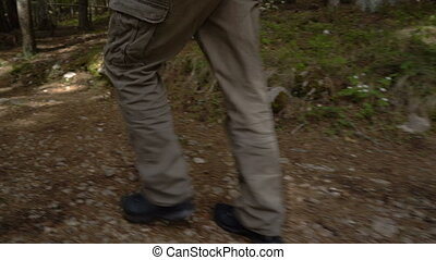 feet of a man walking along a path through the forest