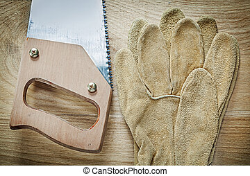 Leather safety gloves sharp hacksaw on wooden board...