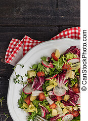 Fresh salad with mixed greens, radish, cheese and tomato in...