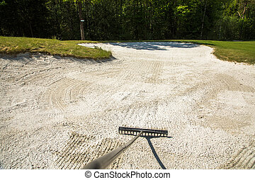 Sand trap, rake in a golf course sand bunkers, raking the sand
