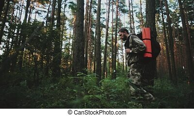 Young ma in overalls with backpack walking through the forest alone. Tourist male spending leisure time in the nature.