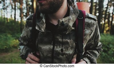 Man in camouflage standing in the forest with backpack and...