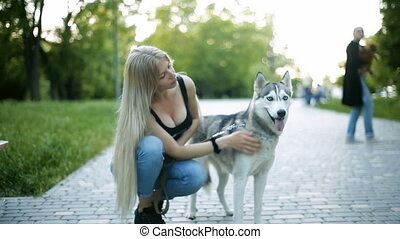 Young blond woman with long flowing hair is walking in the park dog of Husky breed stroked caressed