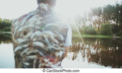 Young man sitting in the rubber boat and fishing at the...