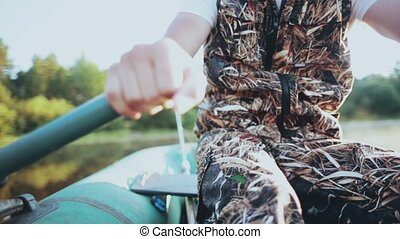 Close-up view of male hands takes the paddles and rows in...