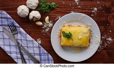 Rectangular Lasagna on a white plate. On a wooden...