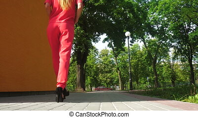 beautiful business woman on high heels and red suit walks...