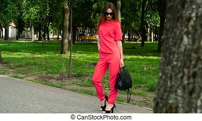 Sexy business woman on high heels in red suit and sunglasses...