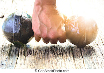 Hand of person holding dumbbell for exercise and healthy under the sunlight