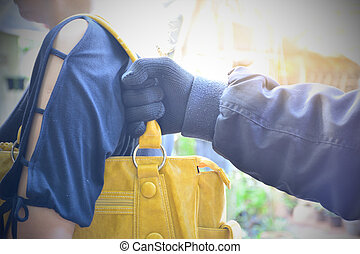 Hand of bandit steal bag another person in the public under...