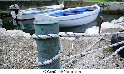 Mooring post on the beach, with mooring cable.