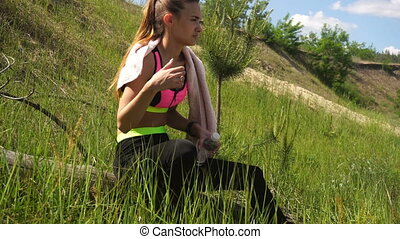 wet girl wipes the sweat after a workout outdoors with a...