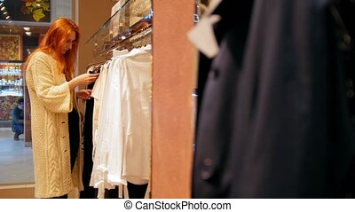 Woman in glasses examines a pink dress in women's clothing store