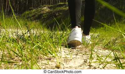 girl in white sneakers walks in summer on the sand and grass...
