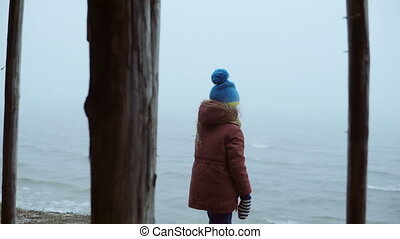 Cute little girl standing on the shore of the ocean and...