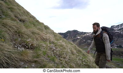 Hiker climbing the mountain slopes - Bearded hiker climbing...