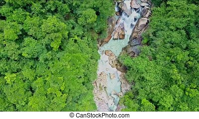Aerial View Camera Moves down to River Creek under Waterfall...
