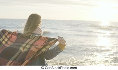 Freedom: young woman standing on shore of sea and raises...