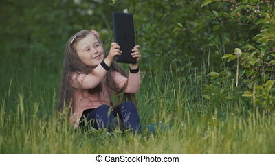 Little girl with a tablet in her hands
