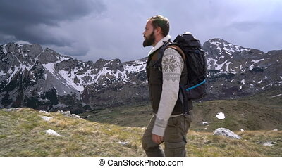 Hiker going along grassy slope against the background of...