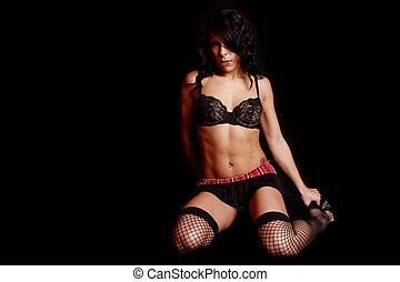 Sexy young woman wearing lingerie with a black background.