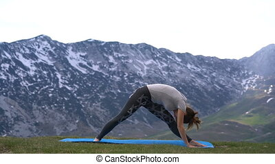 woman practicing yoga outdoors on the background of a snowy...
