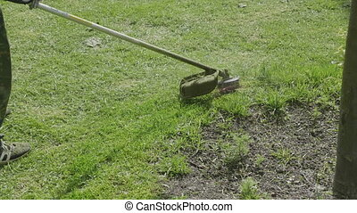 Worker mows green grass manual lawnmower on spring day. FHD...