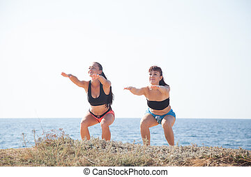 two girls play sports fitness on the beach by the sea