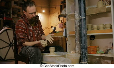 Professional male potter working with clay on potter's wheel...