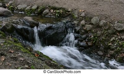 A small stream flows in a hollow among the stones