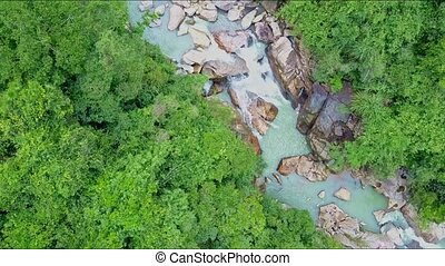 Drone Approaches Close to Green Jungle and Rocky River -...