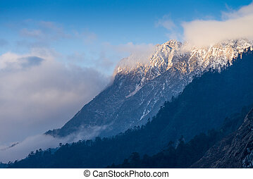 Snowcapped mountain brightened at sunrise in Lachung,...
