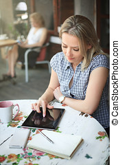 Young woman in cafe uses a tablet for work.