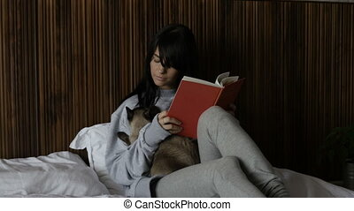 Woman embracing cat reading a book