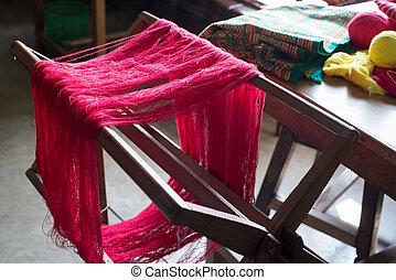 Handloom - Red weaving yarn hung on a handloom